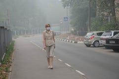 Mujer que recorre en niebla con humo gruesa Imagen de archivo libre de regalías