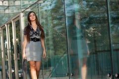 Mujer que recorre a lo largo de la pared de cristal Imágenes de archivo libres de regalías