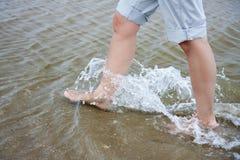 Mujer que recorre a través del agua Fotos de archivo libres de regalías
