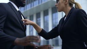 Mujer que regaña al empleado afroamericano, discriminación racial en el lugar de trabajo almacen de metraje de vídeo