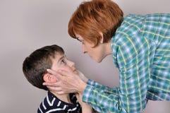 Mujer que regaña a un muchacho joven asustado Imagen de archivo libre de regalías