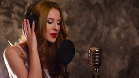 Mujer que registra una canción en estudio de la música, cámara lenta almacen de video
