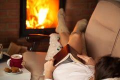 Mujer que relaja por el fuego con un buen libro algunas galletas y caliente Imagen de archivo