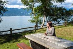 Mujer que relaja y que admira el paisaje en un Parkon costero Sunny Summer Day fotos de archivo