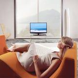 Mujer que relaja y que ve la TV Imagen de archivo