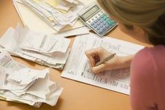 Mujer que rellena el impreso de impuesto Foto de archivo libre de regalías