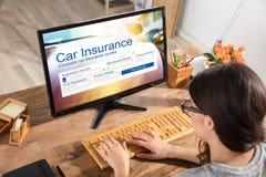 Mujer que rellena el impreso del seguro de coche en el ordenador imagen de archivo libre de regalías
