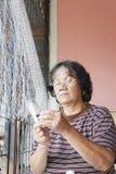 Mujer que repara una red de pesca Imagenes de archivo
