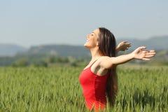 Mujer que respira el aire fresco profundo en un campo Imagenes de archivo