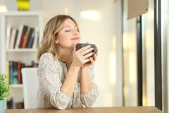 Mujer que respira sosteniendo una taza de café en casa imagenes de archivo