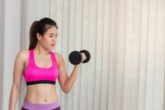 Mujer que resuelve hombros con la pesa de gimnasia, entrenando en centro de aptitud Fotos de archivo