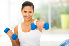 Mujer que resuelve pesas de gimnasia Foto de archivo libre de regalías