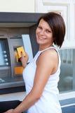 Mujer que retira el dinero de de la tarjeta de crédito en la atmósfera foto de archivo libre de regalías