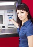 Mujer que retira el dinero de de la tarjeta de crédito en la atmósfera Imagen de archivo libre de regalías