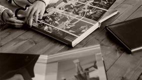 Mujer que revisa las páginas del álbum de foto almacen de metraje de vídeo