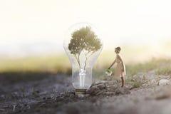 mujer que riega su planta que necesita energía a una bombilla imagenes de archivo