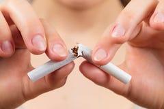Mujer que rompe un cigarrillo Imagenes de archivo