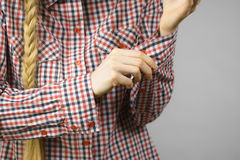 Mujer que rueda encima de las mangas en camisa comprobada Fotos de archivo
