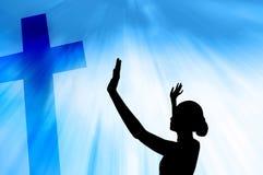 Mujer que ruega bajo cruz Foto de archivo libre de regalías