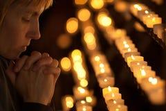 Mujer que ruega en iglesia Imagenes de archivo