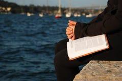 Mujer que ruega en la biblia Imagen de archivo libre de regalías