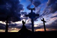 Mujer que ruega en la cruz en puesta del sol Imagen de archivo