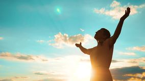 mujer que ruega en sus rodillas la muchacha dobló sus manos en silueta del rezo en la puesta del sol vídeo de la cámara lenta de  almacen de metraje de vídeo