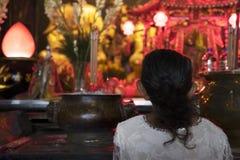 Mujer que ruega en templo Foto de archivo
