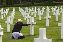 Mujer que ruega en un cementerio conmemorativo Imágenes de archivo libres de regalías