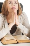 Mujer que ruega para aprobar el examen Foto de archivo libre de regalías
