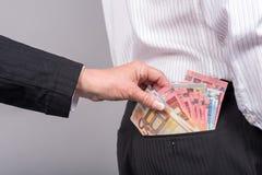 Mujer que saca el dinero del bolsillo trasero Foto de archivo