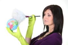 Mujer que saca el polvo de un globo Fotografía de archivo libre de regalías