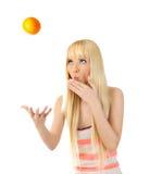 Mujer que sacude encima de una naranja Imagen de archivo
