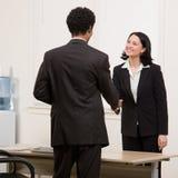 Mujer que sacude las manos con el compañero de trabajo en el escritorio Foto de archivo libre de regalías