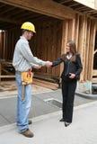 Mujer que sacude las manos con el hombre de la construcción Fotos de archivo libres de regalías