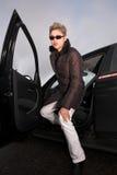 Mujer que sale de su coche Foto de archivo libre de regalías