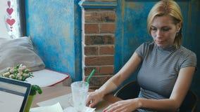 Mujer que sale de una tabla en un café almacen de metraje de vídeo
