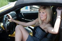 Mujer que sale el coche de deportes de lujo Foto de archivo