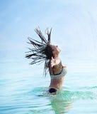 Mujer que salpica el agua con su pelo Foto de archivo libre de regalías
