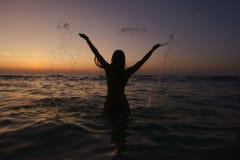 Mujer que salpica el agua en el mar Fotos de archivo