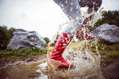 Mujer que salpica en charcos fangosos Fotografía de archivo