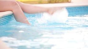 Mujer que salpica pies en la piscina almacen de video