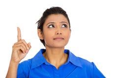 Mujer que señala con el dedo índice y que mira hacia arriba Foto de archivo libre de regalías