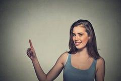 Mujer que señala con el finger hasta lado en el espacio vacío de la copia Imagen de archivo libre de regalías