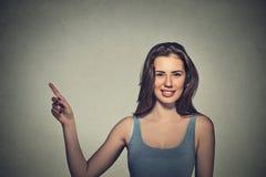 Mujer que señala con el finger hasta lado en el espacio vacío de la copia Foto de archivo libre de regalías