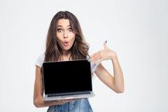 Mujer que señala el finger en la pantalla de ordenador portátil en blanco Imagen de archivo