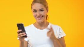 Mujer que señala el finger en smartphone y que dice guau, aprobación del uso almacen de metraje de vídeo