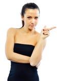 Mujer que señala en el copyspace contra el fondo blanco Fotos de archivo libres de regalías