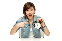 Mujer que señala en el reloj de alarma Fotografía de archivo libre de regalías