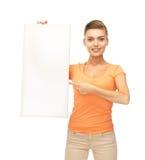 Mujer que señala en el tablero en blanco blanco Foto de archivo libre de regalías